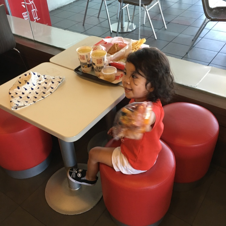 child with Happy Meal toy in McDonald's